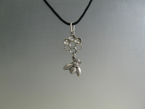 Honey comb and bee pendant. Symmetrical, 7 cell  sterling silver pendant with sterling bee dangle on a black cotton cord.