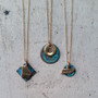 The necklace in the middle is - http://www.mfloritajewelry.com/patinated-bronze-initial/