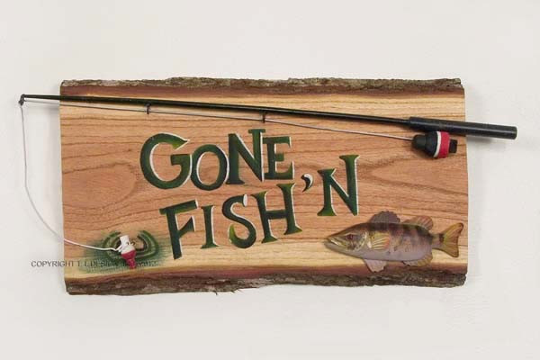 Wooden Bass with rod on tree bark sign lets everyone know were you ...