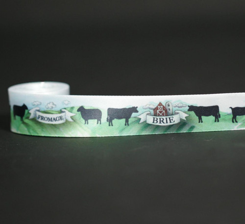 Cheese themed ribbon with cows, goats and sheep grazing in a green pasture with mountains and a traditional red barn in the background. This artfully designed ribbon makes the perfect tie for a gift for the cheese lover in your life.