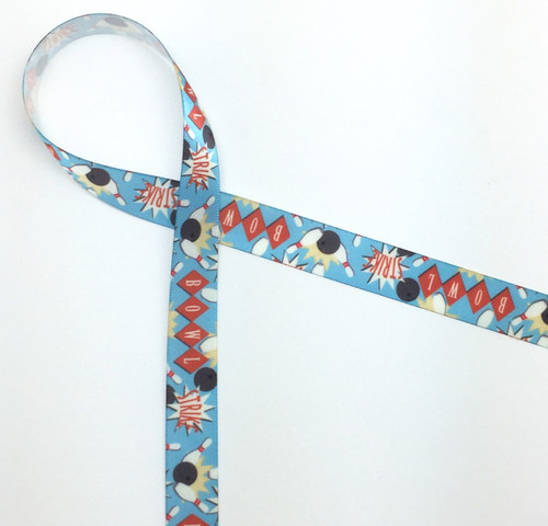 Bowling themed ribbon on a light blue background featuring bowling balls, pins in red and white and the words Bowling and Strike across the ribbon carries a vintage theme throughout. Designed and printed in the USA