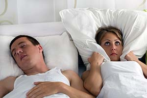 snoring man in bed with annoyed sleep partner