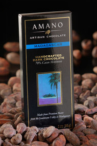 Madagascar 70% Dark Chocolate Bar on a bed of cocoa beans.