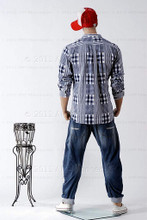 In this full body rear view photo, wearing a red cap, blue jeans, tennis shoes, and an open plain shirt showing a white t-shirt, mannequin Ken, stands with his legs even with his arms straight at his sides - hands in fists.  Mannequin Ken can be displayed with or without a wig / hairpiece.  Glass stand and support hardware included.