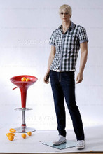 In this full body view photo, wearing a short blond wig / hairpiece, blue jeans, tennis shoes, and a plaid short-sleeved shirt, mannequin Alex stands with his left leg slighly forward along with his left arm while his right remains back - both at about hip level.  Mannequin Alex can be displayed with or without a wig / hairpiece.  Glass stand and support hardware included.