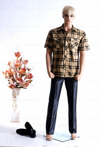 In this full body view photo, wearing a a short blond wig / hairpiece, plaid shirt with blue jeans, mannequin Mike, stands with his left light slighly forward with his arms straight at his sides - hands in fists.  Mannequin Mike can be displayed with or without a wig / hairpiece.  Glass stand and support hardware included.