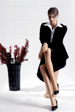 In this full body view, wearing a black business suit with a white blouse and heels, mannequin Ruby sits with her right leg crossed over her left and her right hand resting on her right knee. Her left hand rests on her left knee.   With pierced ears, mannequin Ruby can display earrings and jewelry.  Pedestal included.