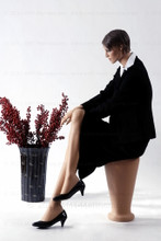 In this full body side view, wearing a black business suit with a white blouse and heels, mannequin Ruby sits with her right leg crossed over her left and her right hand resting on her right knee. Her left hand rests on her left knee.   With pierced ears, mannequin Ruby can display earrings and jewelry.  Pedestal included.