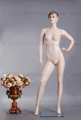 In this full body view photo, naked mannequin Betty is in a neutral stance with her right leg slightly forward.  Her left arm is bent with her hand resting above her waist while her right arm is almost straight down with her hand at hip level.  With pierced ears, mannequin Betty can display earrings and jewelry.  Glass stand and support hardware included.