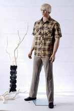In this full body side view photo, wearing a short blond wig / hairpiece, grey slacks, black loafers, and a tan plaid shirt, mannequin Ed, stands with his legs apart in even stance with his arms straight at his sides.  Mannequin Ed can be displayed with or without a wig / hairpiece.  Glass stand and support hardware included.