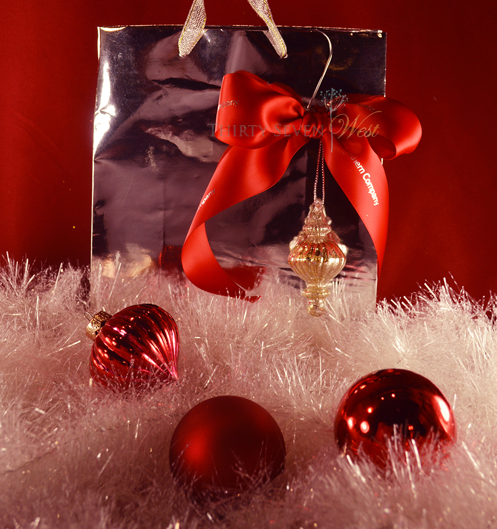 Custom printed red ribbon with silver logo or lettering paired with silver bag and ornament.  Simple statement with elegant gift bag makes any gift more impactful.
