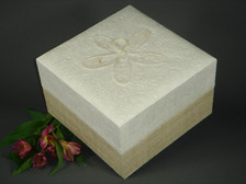 This Embrace White Hemp  Earthurn features a hemp covered base and a simple handmade paper top. Inlaid into the top of this attractive urn is floral material crafted by hand into the shape of a flower.