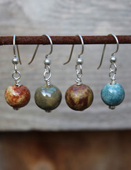 memorial earrings with cremation ash fired into the glaze. colors shown l to r : calico, sage, terra, sky