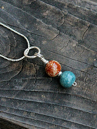Nexus memorial necklace shown with 2 Sisu Beads (calico and sky) on the optional silver chain.