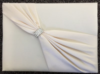 "Ivory Satin Sash Guest Book. This elegant ivory satin guest book is decorated on the front with an ivory satin sash and rhinestone ornament. The book measures 8.5"" x 6"" and holds 55 pages for a total of 990 signatures."