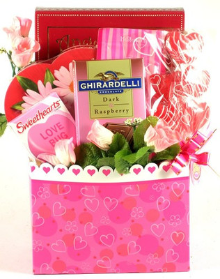 Pink valentine gift box filled with a heart filled with chocolates and a variety of candy.