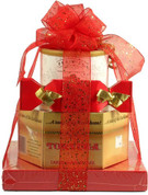 Gold boxed Cake, boxed Chocolates, container of nuts, all stacked and tied with a red ribbon.