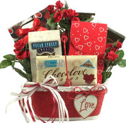 Red gift basket trimmed in white filled with an assortment of chocolates.