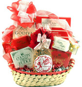 A gift basket trimmed in red filled with truffles and snacks.