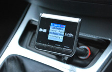 A close up of the JustDAB cigar lighter DAB car kit. Displaying Radio 1 Xtra on the colour screen