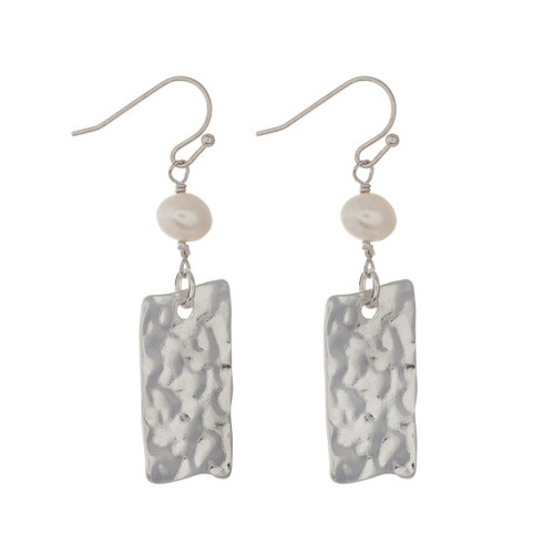 """Silver tone fishhook earrings displaying a faux fresh water pearl with a hanging hammered plate. Approximately 1 1/2"""" in length."""