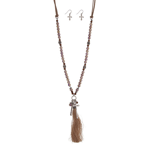 "Light brown cord half beaded necklace set displaying purple, brown, and burnished silver tone beads, a plate stamped ""BLESSED"", a cross charm, and a 4"" fabric tassel. Approximately 29"" in length."