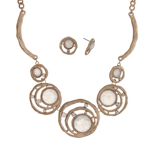 "Matte gold tone necklace set displaying layered rings with white cabochons and rhinestone accents. Approximately 17"" in length."