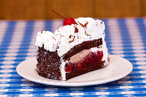 This is our number selling cake that is perfect for any special occasion! It is always fresh and made!  Our Black Forest Cake is made with moist chocolate cake, rum, imported cherry preserve and whip cream. It is then decorated with whip cream, all-natural cherries and shaved chocolate pieces on top.