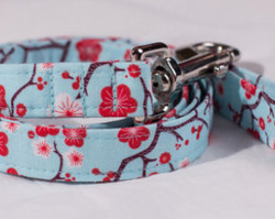 "Cherry Blossom Blue Chasin' Tail Leash  Chasin' Tail Doggie Designs are special handmade creations.  Each piece is made by hand, with care, in Boring Oregon.  Chasin' Tail handcrafted leashes are 5 feet in lenght available in 3 widths.  They feature a durable swivel hook.  Leashes are made from a washable fabric.  Gently wash and hang to dry.  Chasin' Tail dog leashes can be ironed with a cool iron to remove wrinkles if they should appear.  Chasin' Tail leashes come in the following widths.   SM 5/8"" wide  Med 3/4"" wide  LG  1"" wide  Chasin' Tail also offers matching handmade collars and cute collar accessories like Bow Ties and Flowers.  Look for them to order and complete your pet's special look."