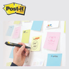 Person writing on a post-it note