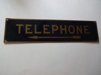 Old brass  payphone sign for wooden phone booth