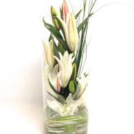 Glass cylinder vase filled with white oriental lilies.