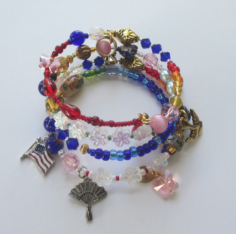 The beads of the Madama Butterfly Opera Bracelet symbolize the narrative of Puccini's opera. A flag charm represents U.S. Naval Officer Pinkerton a fan evokes the delicate Cio Cio San who is also represented by pink crystals and butterflies.