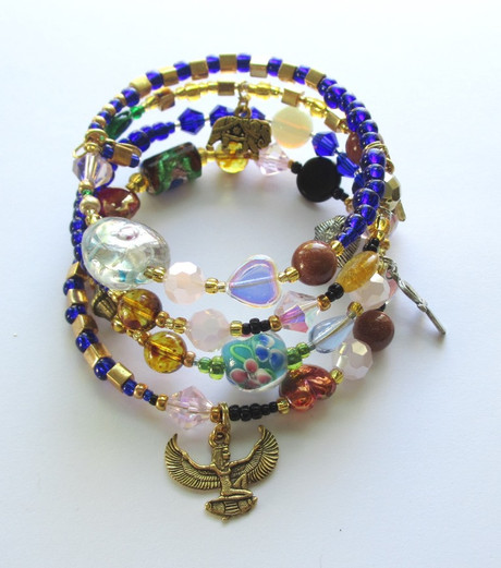 """The charm of the goddess Isis symbolizes Amneris's final prayer that the gates of heaven be opened to Radames and Aida. The clear iridescent heart bead -top layer- indicates Radames pure love for Aida which he declares in the famous aria """"Celeste Aida""""."""