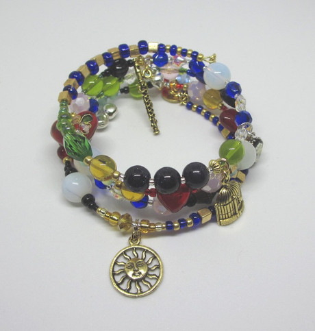 Deep blue and gold colored glass beads evoke the riches of ancient Egypt; luminous sea opal beads represent the Queen of the Night. Beads and charms symbolize the story of  Die Zauberflote...