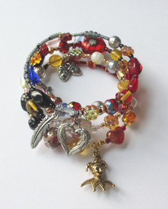 """View of the Rigoletto Bracelet highlighting the Jester charm indicative of Rigoletto (bottom); and the masks charm (top) which symbolizes Rigoletto's words of frustration from Act 1 """"To be permitted nothing but to laugh! I'm denied that common right, to weep."""""""