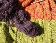 Three colour knitted throw rug in extra thick linen. Plum, tangerine and lime