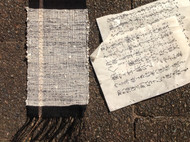 Woven sample with black ramie and thin strips of paper from a Japanese novel.