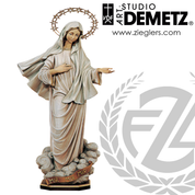 The Our Lady of Mddjugorje statue in hand-carved linden wood or fiberglass with choice of 38 48 or 60 inches in natural stain color bronze or white marble finish crafted in Italy DM798