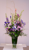 A soft melange of purple, mauve, lavender and a touch of pink. Mixed foliage such as ruscus, salal, lily grass and curly willow. We have used Larkspur, Anastasia mums, Iris, Alstroemeria and roses.