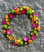 Customer wanted a very vibrant and colourful wreath. In the flower shop our florists used Ontario grown hot pink Gerbera, local purple statice, flat yellow chrysanthemums, green Revert mums and large bloomed Hig and Magic Roses. The wreath is 36 inches across.
