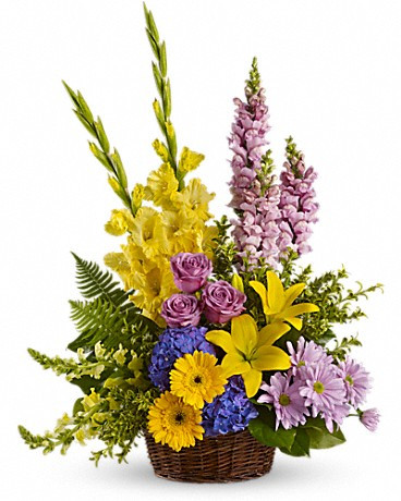 Tall flower arrangement in mixed flowers, in purple and yellow tones delivered by Italian florists.