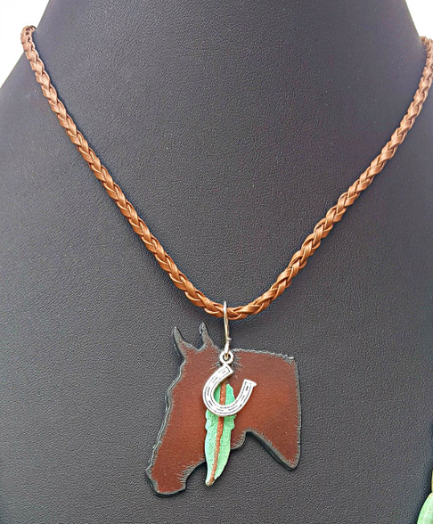 """Rustic Horse Head Necklace. On Adjustable Faux Leather Cord. PROUDLY HANDMADE IN THE USA This listing is for Horse Head necklace only. Layers well with other necklaces. Shown with 52"""" Turquoise Green Howlite necklace available on request-$60 Rustic Bronze Horse Head Pendant, with Verdigris Green Patina Feather and Silver Horseshoe Charms. 16.5""""-18"""" long. Other charms available on request.  Pistol, Arrow, Dragonfly, Kokopelli available instead of the horseshoe."""