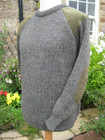 Hand framed crew neck sweater in green derby tweed mix with patches on shoulders and elbows.