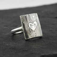 Custom engraved initials on a tree trunk ring