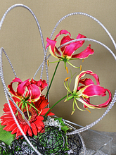 Playful arrangement of orchids and gerbera with wire accents.
