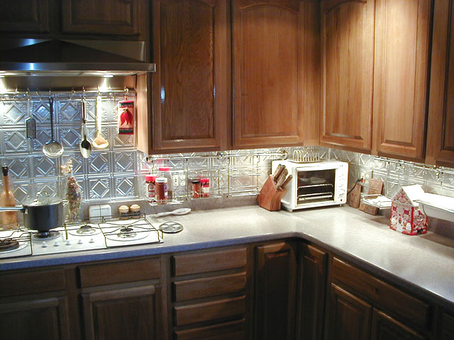 Beautiful kitchen with Dark Cabinets and Diamond Backs stainless steel looking backsplash.