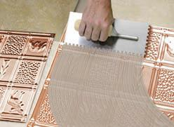 Using a trowel the glue is applied to the back of the metal backsplash tiles.