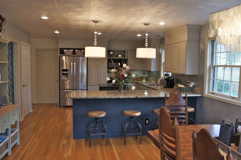 After image of a kitchen by bella tucker. Paitned cabinets, new ceiling lighting fixtures.