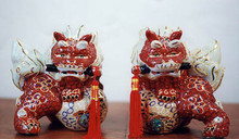 "Protective Red Lions (PAIR) Back again...A duo of large, handsome, beautifully adorned Lions, holding tasseled swords in their teeth to protect YOU! The Lion is sacred to Buddhism; a pair is often placed to guard the gates of temples, official buildings and homes. They are a symbol of valor, energy and wisdom. 7"" tall, 8"" wide. Ceramic. The price is for 2. Item #FSE-GP-2PLR."